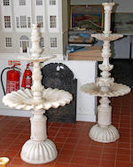 A marble terrace table,pierce-carved with formal scroling foliage, 107 x 46cm, on square column and a fountain with two circular graduated lobed dishes, 70 x 60cm diameter and a square section jardiniere carved with stiff leaves