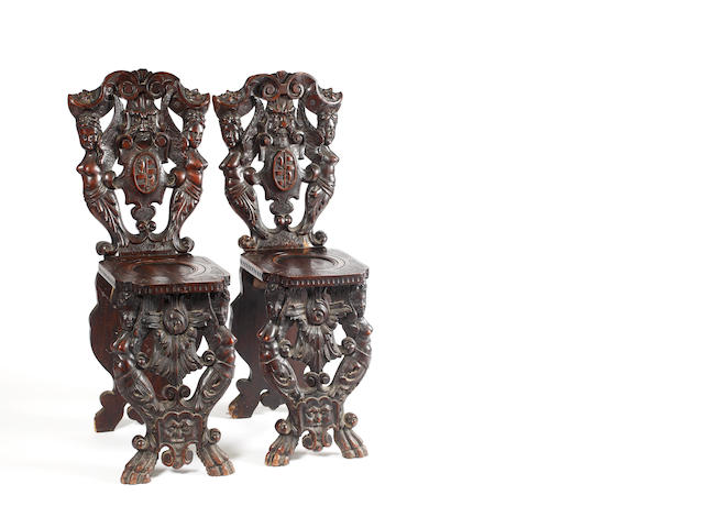 A pair of early 19th century Continental carved walnut hall chairs,