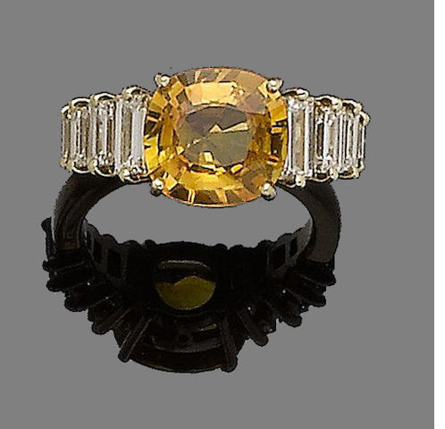 A yellow sapphire and diamond ring