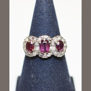 A three stone ruby and diamond chip ring