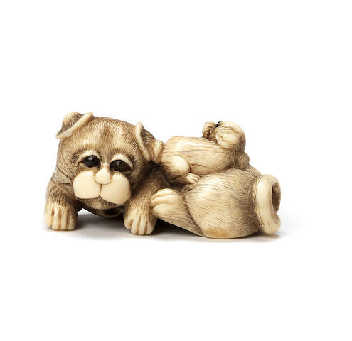 An ivory netsuke of a dog and pup By Tomokazu, Kyoto, early 19th century