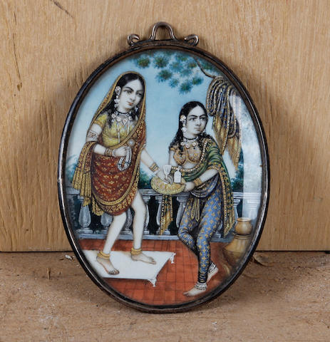 Indian School, circa 1900 A miniature of a young princess or courtier offered refreshment by a female attendant, oval