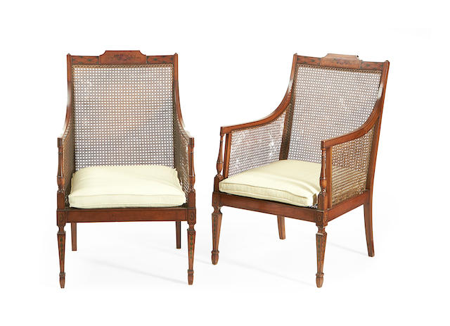 A pair of Edwardian satinwood and polychrome decorated caned bergeres  in the Sheraton revival style