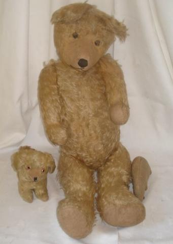 An oversize blonde plush teddy bear, with stitched eyes and nose, hump back jointed limbs and felt pads, 87cm, a rabbit with boot button eyes, 19cm, and a blonde plush standing dog with glass eyes stitched nose and mouth, 24cm. (3)