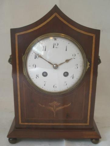 "A late Victorian mantle clock, the 4"" enamel dial with Roman chapter in an inlaid mahogany pagoda top case with side mask and ring handles, with key and oil can, 27cm."
