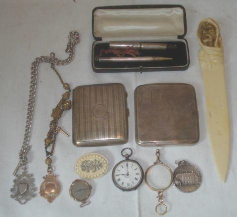 Two silver engine turned cigarette cases, a cased engine turned cased small sized fountain pen and propelling pencil stamped 'Sterling', cased, a graduated silver Albert watch chain and engraved fob, a 9ct engraved watch fob on rolled gold dress watch chain, a pair of 19th Century rolled gold folding glasses, a silver cased fob watch, a 9ct gold watch head, bone brooch, a French medallion, and an ivorine Arab head paper knife.