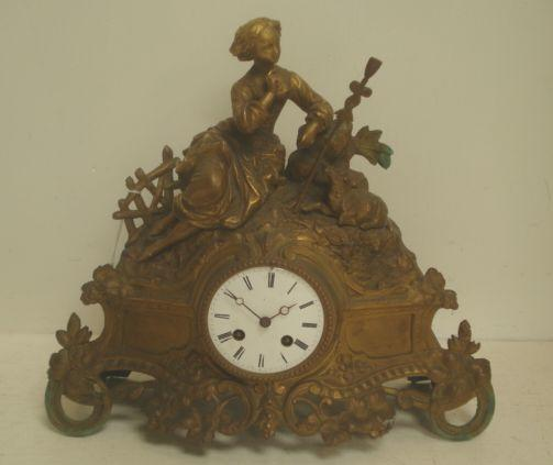 A French gilt speltar mantel clock, 2nd half 19th Century, surmounted by a shepherdess and sheep, the 8 day movement striking on a bell, with key, 33cm.