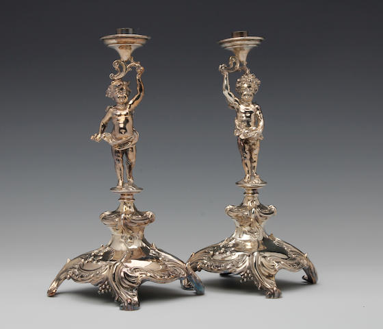 A German silver pair of cherub lamp bases by Bruckmann and Sohne, Heilbronn, retailed by Posen, circa 1910