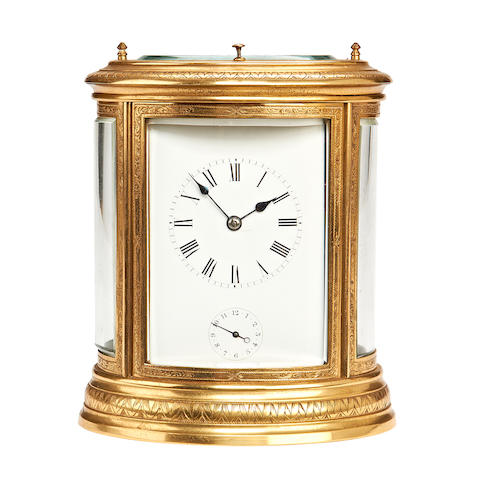 A late 19th / early 20th century Swiss gilt brass engraved oval carriage clock with repeat and alarm