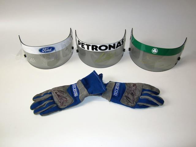 Three signed Formula 1 helmet visors and one pair of signed gloves,