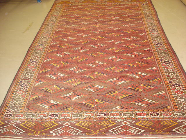 Afghan rug, terracotta field with all over geometric motifs, spurious date to multiple borders 320cm x 190cm Purchased Libertys