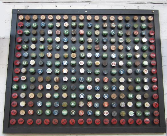 A large framed display of assorted oil bottle caps,