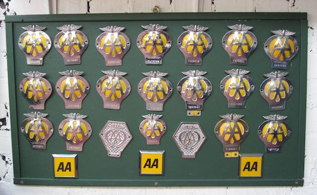 A framed display of Automobile Association member's badges,