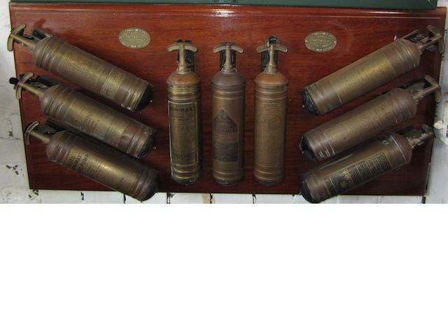 A display board of nine motoring fire extinguishers,