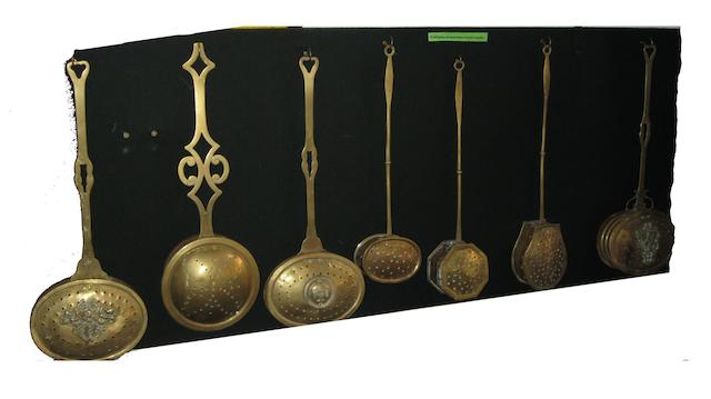 A display of brass chestnut roasting pans,