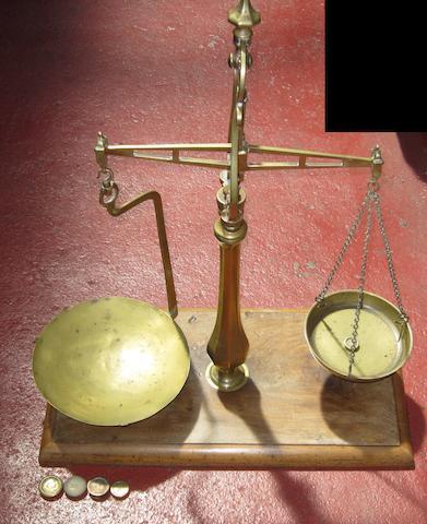 An ornate brass shop counter balance,