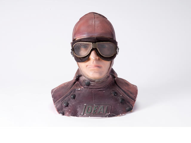 A painted plaster shop display bust for the sale of motoring goggles,