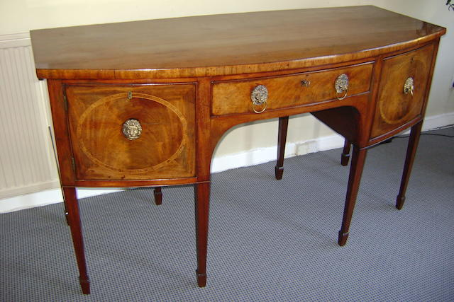 A George III mahogany sideboard, the bow front fitted with cellarette drawer, napery drawer and cupboard, inlaid with kingwood oval crossbandings, on tapered lozenge section front legs, 168cm wide, 95cm high, 70cm deep