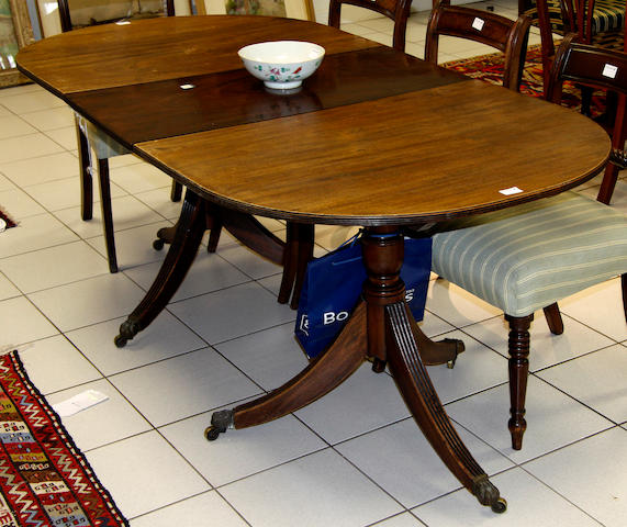 A reproduction Regency style mahogany twin pillar D-end dining table