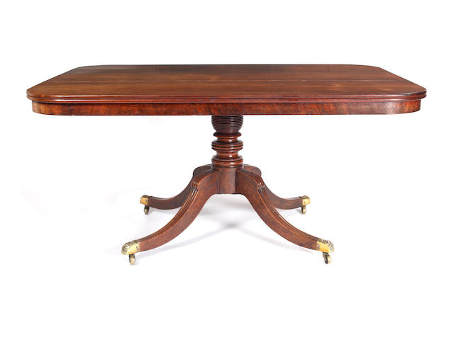 A Regency mahogany breakfast table, the rectangular moulded edge tilt-top with rounded corners, on a ring turned pillar, the moulded downswept quadripartite base with cast brass caps and castors, 152 x 115cm.