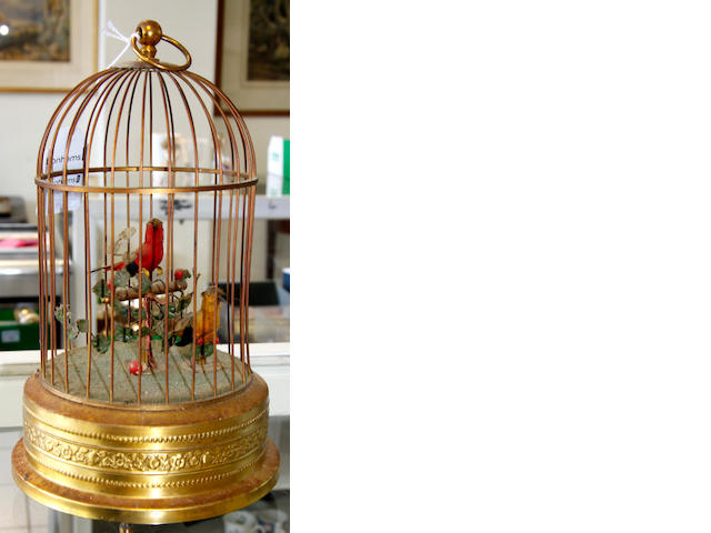 A 1950's singing bird automaton,the cage containing two birds, a pocket barometer by Negretti & Zambra in leather case, a horn beaker, a trio of Great War medals and three framed pot lid: Hide & Seek, both alike & The Poultry woman