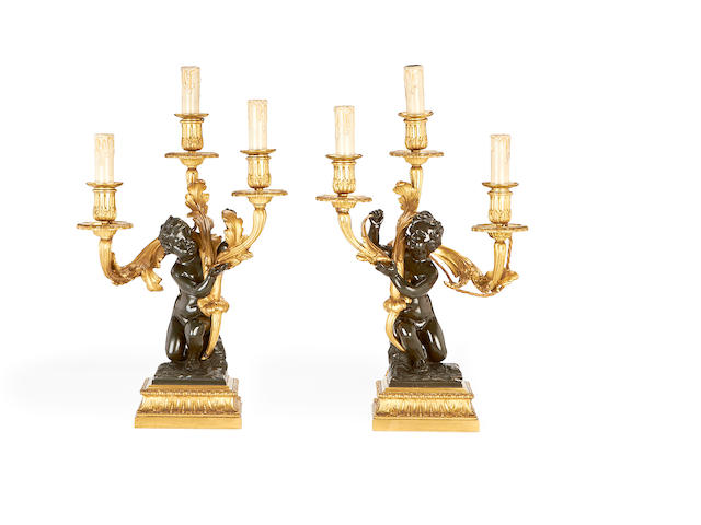 A pair of mid 19th century Rococo Revival gilt and patinated bronze figural candelabra