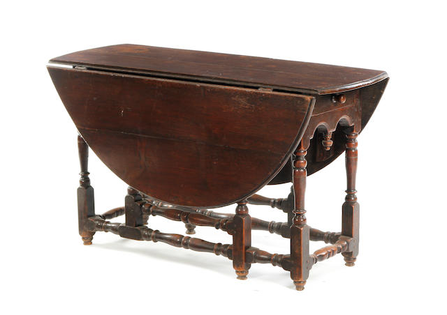 A 17th century walnut gate-leg table, the top replaced, raised on turned legs, united by a rail stretcher – Width 119cms, Height 70cms