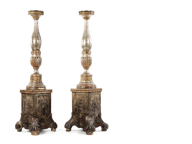 A pair of silver-gilt carved torcheres, decorated with the word 'Antigua' to each side of the base ***ESTIMATE TO BE CONFIRMED SUBJECT TO FURTHER RESEARCH***
