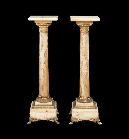 A pair of early 20th century Algerian Onyx and gilt metal mounted pedestals
