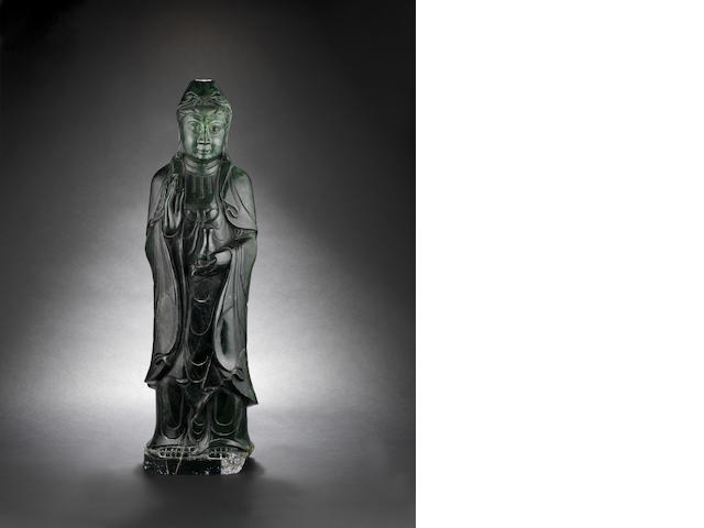 A large, spinach-green jade standing figure of Guanyin