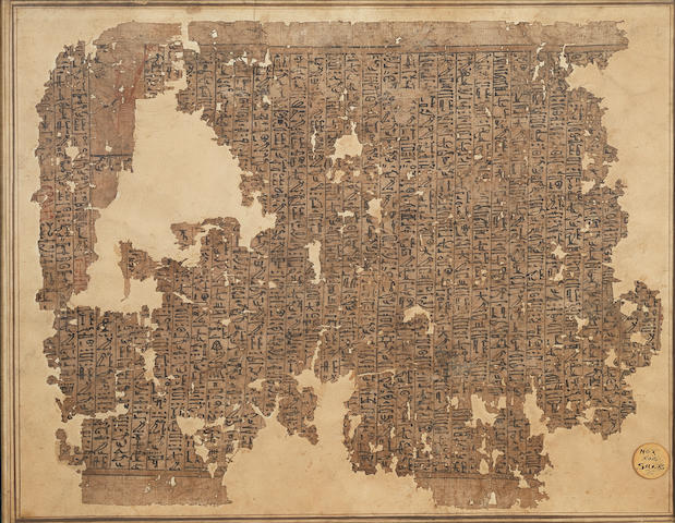 An Egyptian papyrus fragment with script, framed