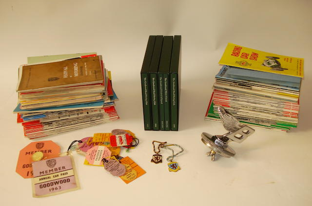 Combined Item: A Bentley forward leaning 'B'mascot and radiator cap, a good collection of 1950s/1960s motor racing programmes, two 1962 Goodwood enamelled members badges and a quantity of paper tickets and Goodwood Road Racing Club books. (Qty)