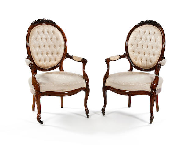A pair of mid-19th century walnut open armchairs