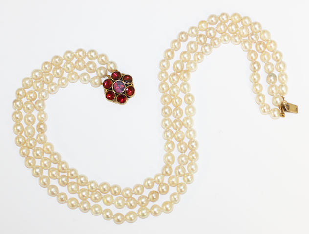A three strand cultured pearl necklace with garnet clasp,