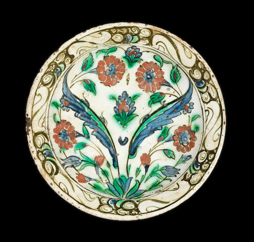 An Iznick pottery plate with polychrome flowers