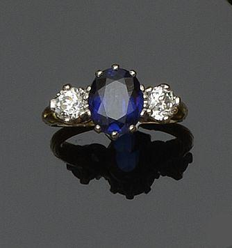 A synthetic sapphire and diamond three stone ring