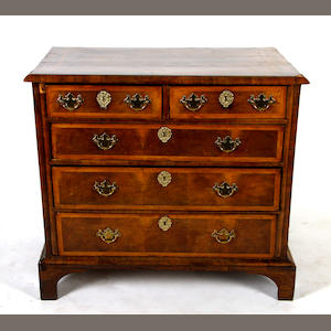 An early 18th Century walnut featherbanded chest, the quarter veneered moulded rectangular top above two short and three long drawers, on a moulded base and later bracket feet, 96cm.
