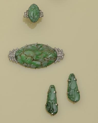 A small collection of jade and diamond jewellery Comprising a ring with oval carved jade panel between stepped diamond set shoulders, shank stamped '18ct', an carved oval jade panel brooch, with millegrain set stepped diamond set shoulders, and a pair of carved jade clips.