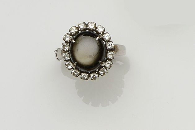 A black star sapphire and diamond cluster ring