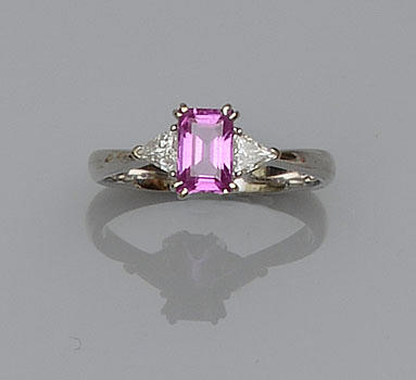 A pink sapphire and diamond three stone ring