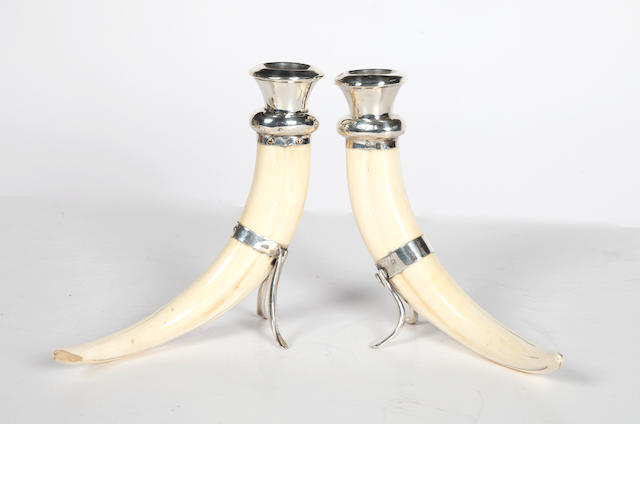 A pair of silver mounted boar tusk canslesticks