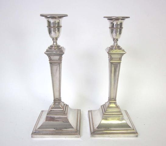 A pair of George III  Old Sheffield plate candlesticks unmarked together with a pair of Old Sheffield plate three-light branch section, hexagonal nozzles, with unusual spiralling ropetwist arms (4)