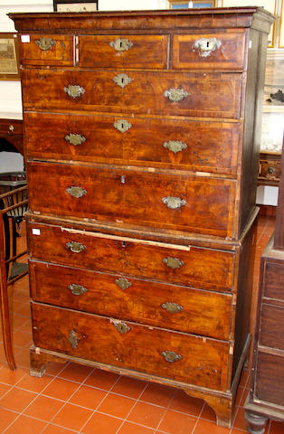 "An early George II walnut tallboy,with ogee cornice, crossbanded and feather banded drawers, original engraved handles (some bows lacking), the side in unveneered oak, distressed, 105cm wide178cm high, (41"" wide70"" high)"