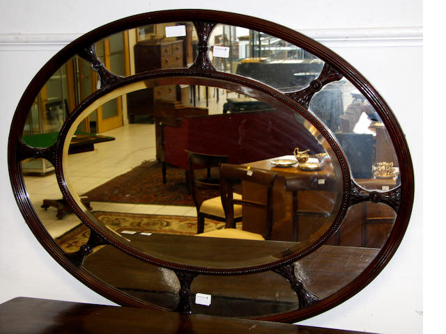 A late 19th Century mahogany oval mirror,