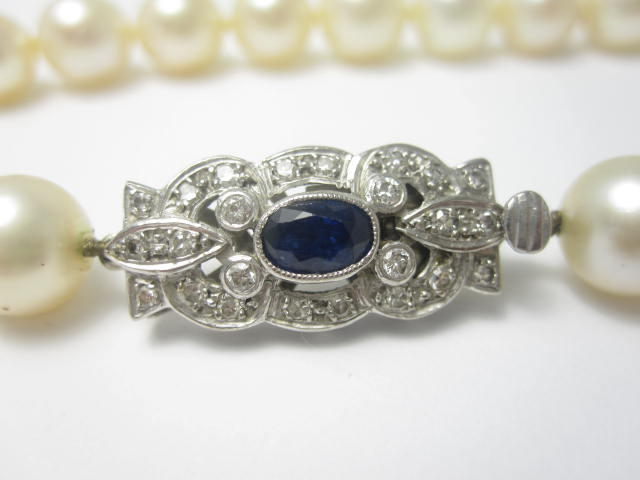 A cultured pearl necklace with a sapphire and diamond clasp