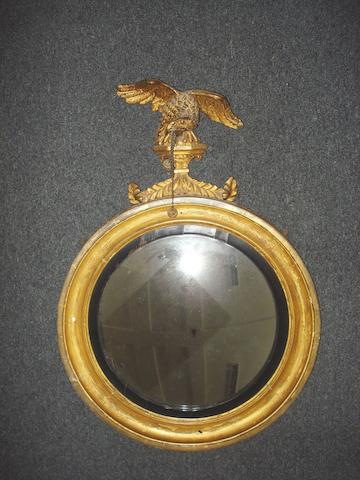 A Regency giltwood circular convex mirror with an eagle finial