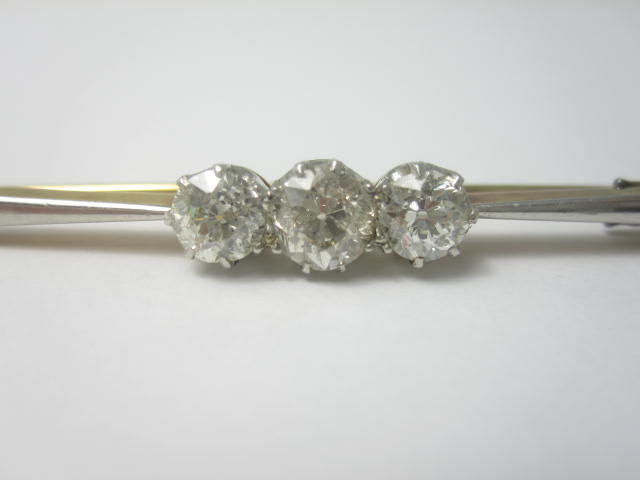 An early 20th century diamond three-stone bar brooch