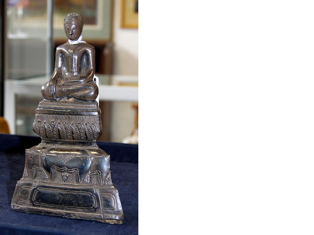 A white metal covered buddha on stand