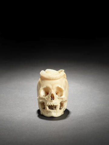 An ivory model of a snake on a skull Meiji Period