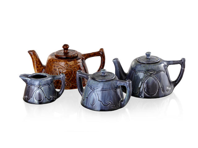 An Art Nouveau Harvey scholl grey glazed earthenware three piece tea set